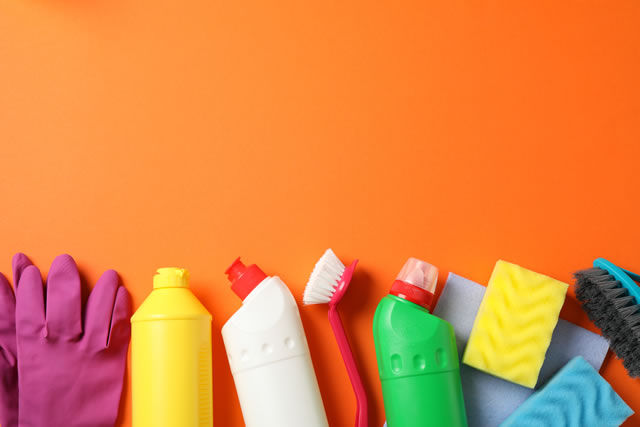 Bottles with detergent and cleaning supplies on orange background, space for text