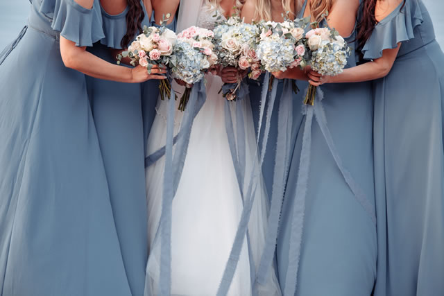 Beautiful blue dridesmaids dresses and bride with fresh hydrangea bouquets