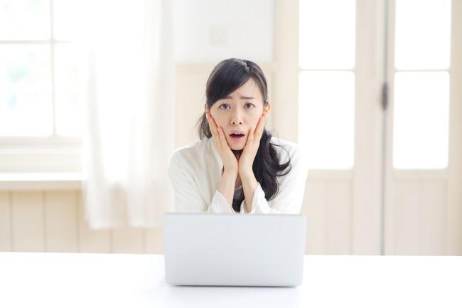 ノートパソコンの前で困った顔をしている女性