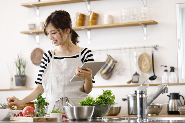 キッチンで料理をする若い女性