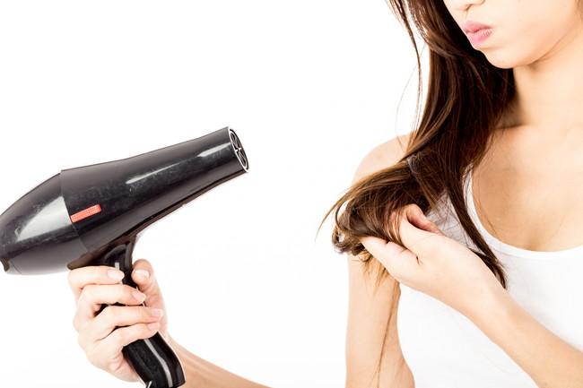 ドライヤーで髪を乾かしながら毛先を気にする女性