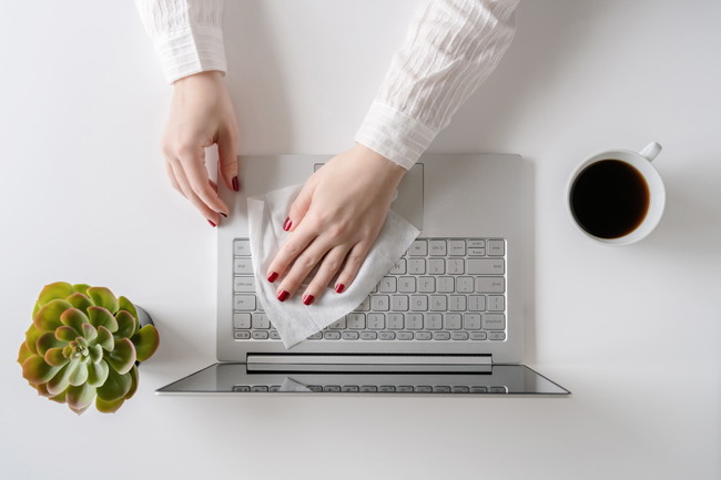 コーヒーカップを近くに置いてノートパソコンを拭く女性の手