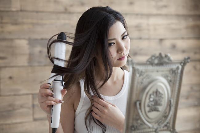小手を使って髪をセットしている女性