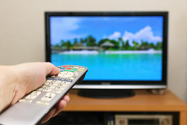 テレビのリモコンを操作する手