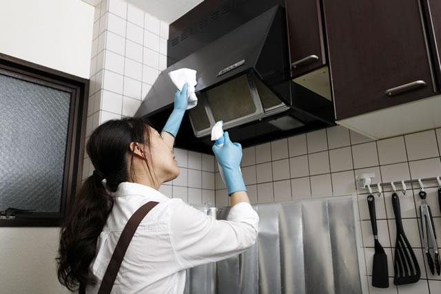 換気扇の拭き掃除をしている主婦