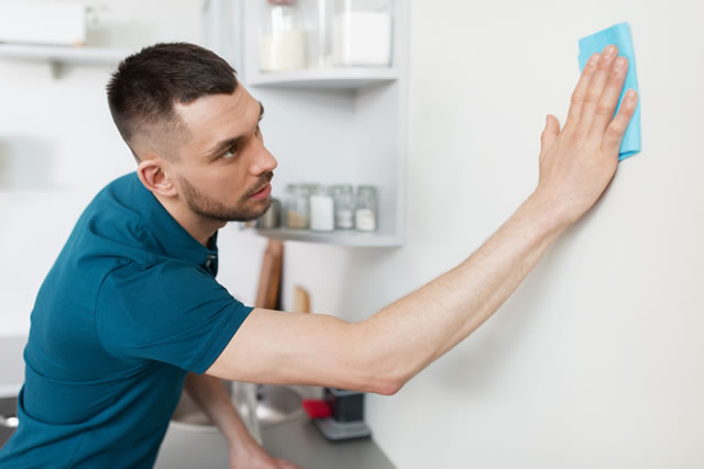household and people concept - man with cloth cleaning wall at home kitchen