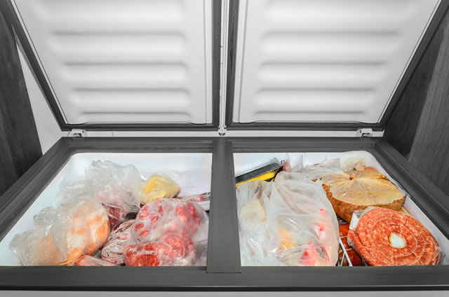 Frozen food in the freezer. Bagged frozen meat and other foods in a horizontal freezer with the two doors open. Food preservation