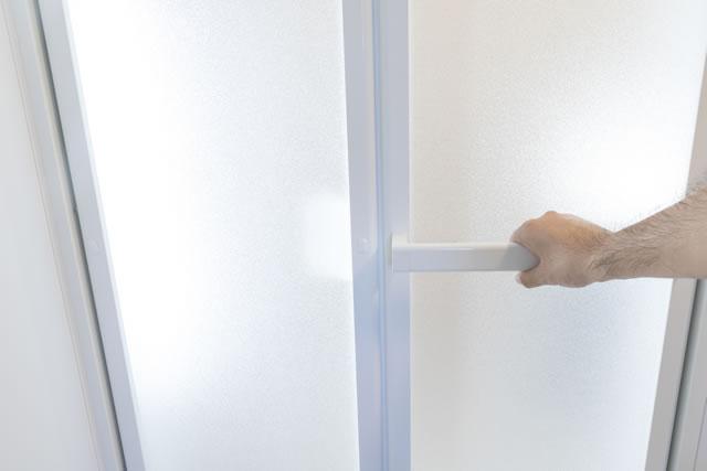 バスルームの扉を開ける手