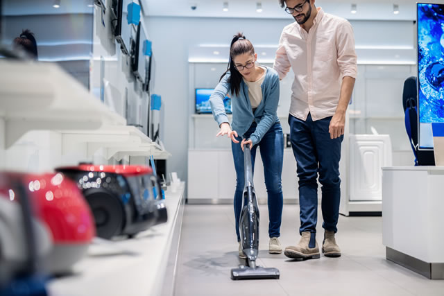 Woman trying out vacuum cleaner in tech store. New technologies concept