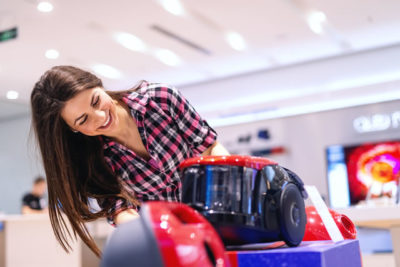 Smiling gorgeous Caucasian brunette with long hair dressed casual looking for new vacuum cleaner while standing in tech store.