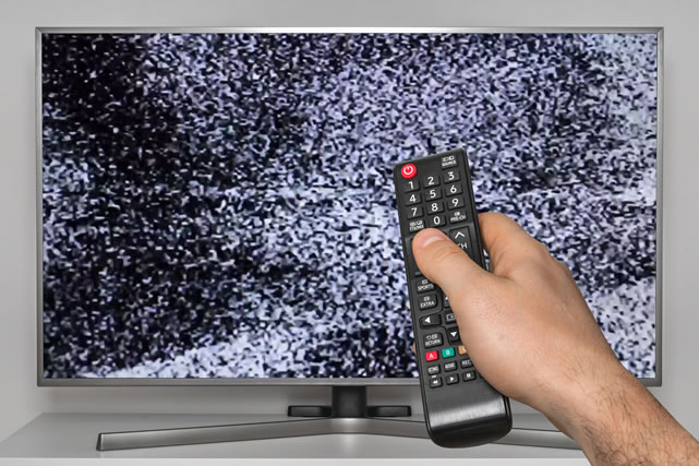 Analog noise on TV and human hand with TV remote control