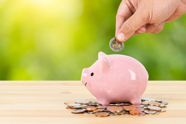 ブタの貯金箱に小銭を入れる手