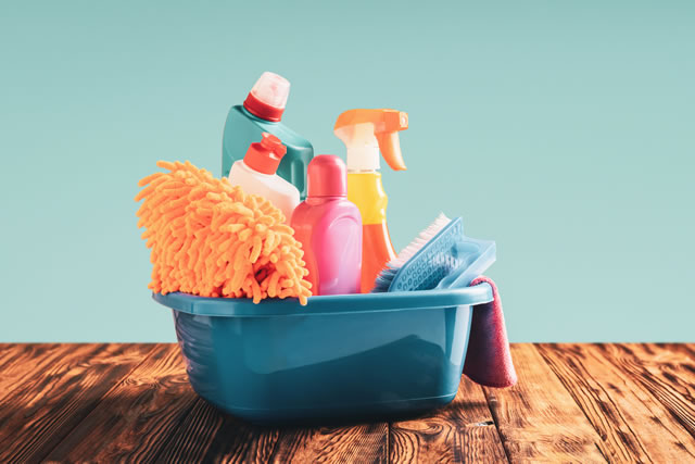 Cleaning items in a basin on a wooden table web banner with copy space: spring cleaning concept