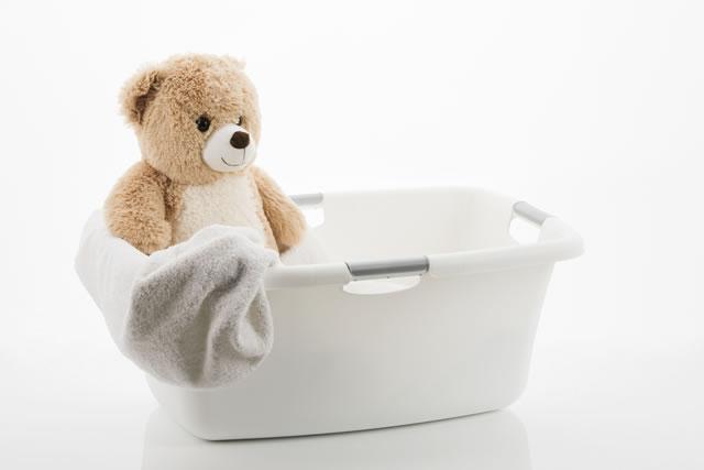 Teddybär, Handtuch und Wäschekorb