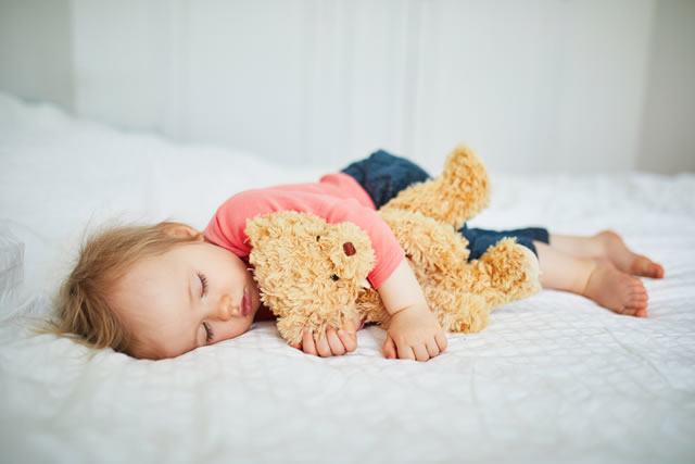 Adorable baby girl sleeping with her favorite toy