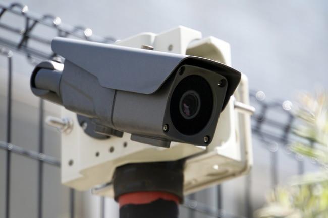 住宅に設置された黒い監視カメラ
