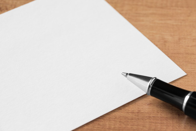 机の上にある紙とボールペン