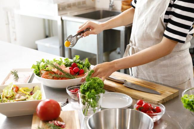 キッチンでサラダを盛り付ける主婦