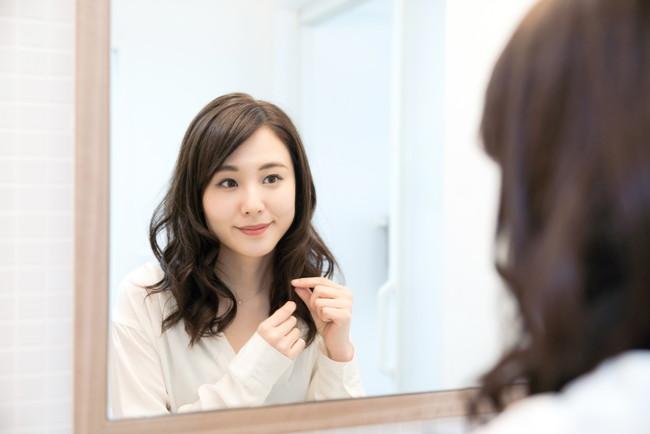 鏡を見ながら毛先を整える女性