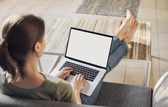 くつろぎながらノートパソコンを使う女性