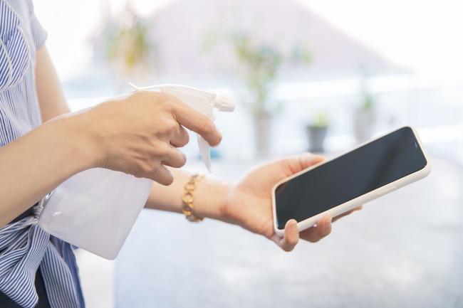 スマートフォンを消毒する女性
