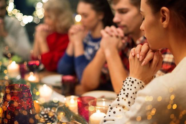 食事の前に手を合わせて祈りをささげる宗教の信者