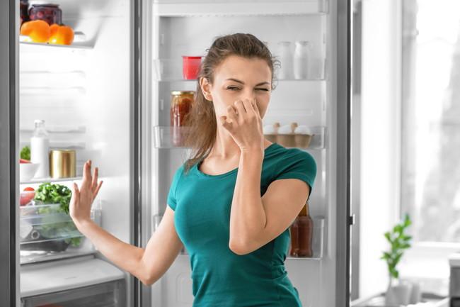 冷蔵庫を開けて鼻をつまむ女性