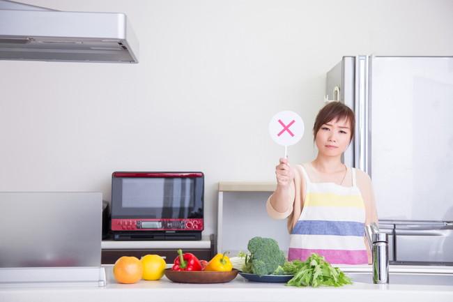 キッチンで×印を見せるエプロン姿の女性
