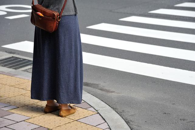 横断歩道の前に立つ紫のスカート女性