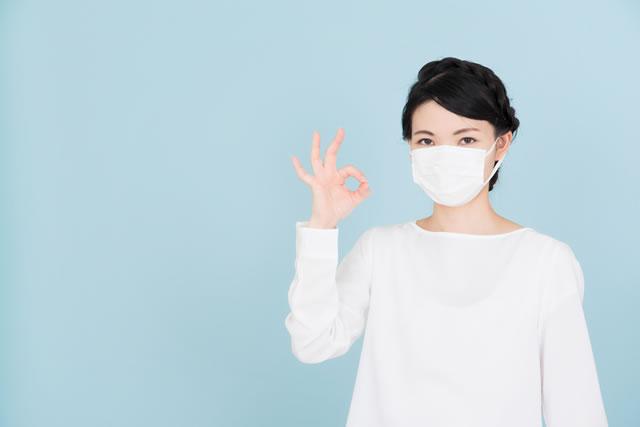 マスクをつけてOKサインする女性女性