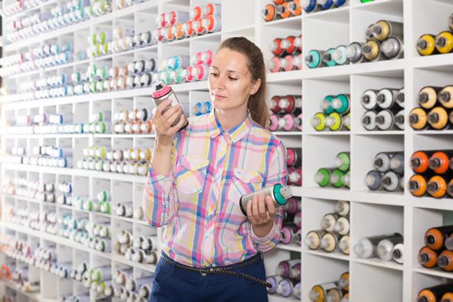 portrait of woman choosing paint color in aerosol can in art shop