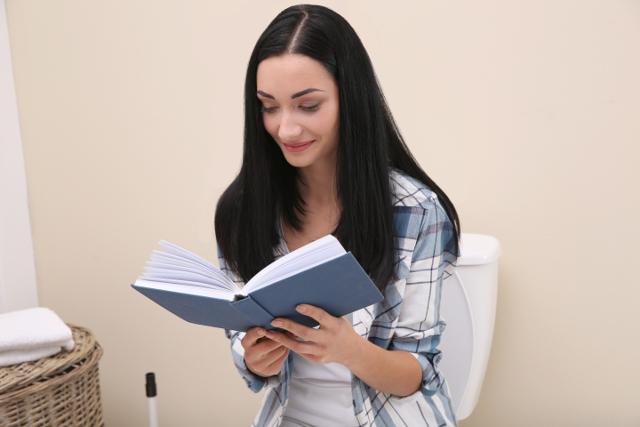 トイレで本を読む女性