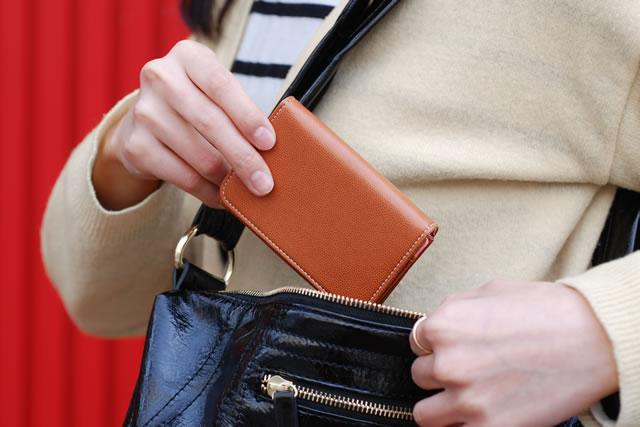 ポーチから財布を出す女性