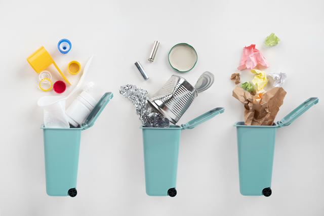 Trash bins and assorted garbage on grey background. Recycle concept