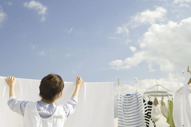 外で服を干す女性