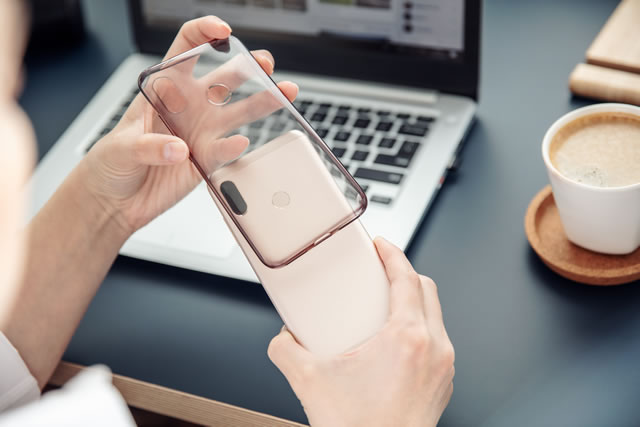 Woman's hands put silicone case on the back side of smartphone