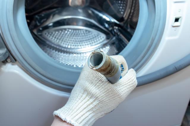 洗濯機の排水ホースを持つ手
