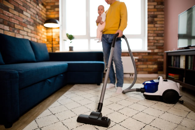 子供を抱えながら家事をする女性