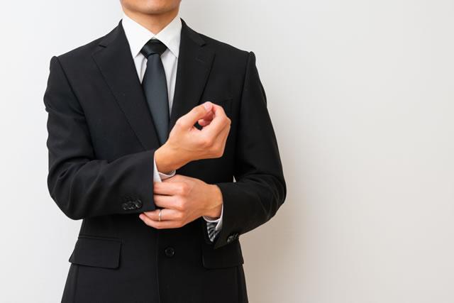 喪服の袖を直す男性