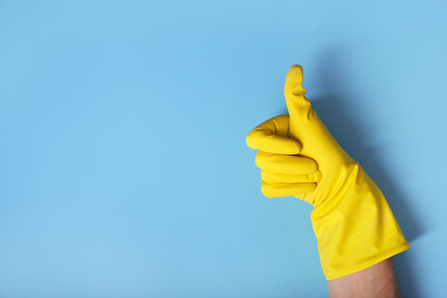 Hands in gloves on blue background. Thumbs up