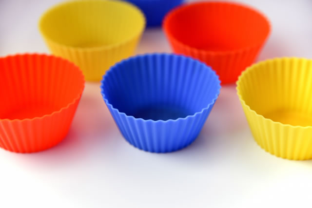 Colourful silicone muffin and cupcake reusable baking liners closeup on white background