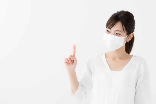 指を立てるマスクの女性