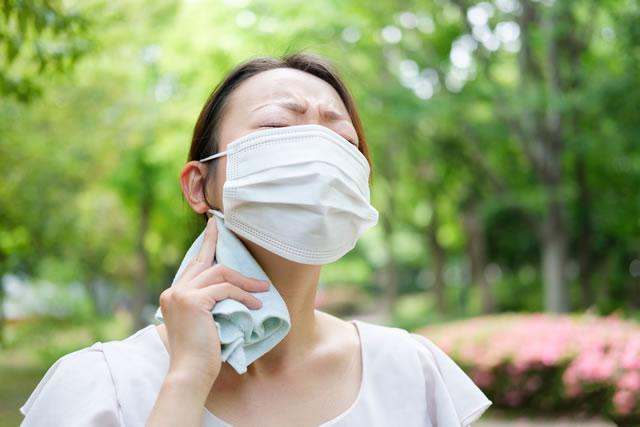 汗を拭くマスクの女性