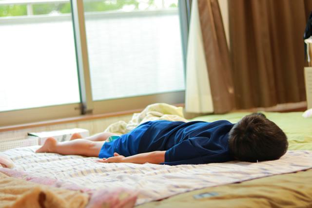 床の上に敷かれた布団で寝る子ど
