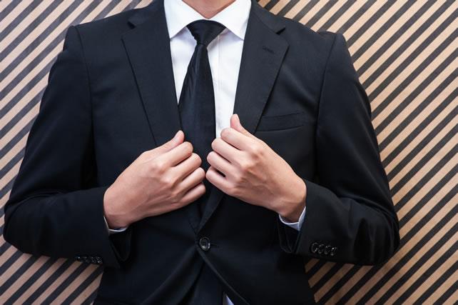 喪服の襟を直す男性