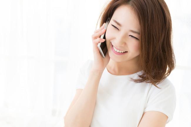 楽しそうにスマートフォンで通話をしている女性