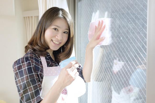 笑顔で窓ふき掃除をする女性