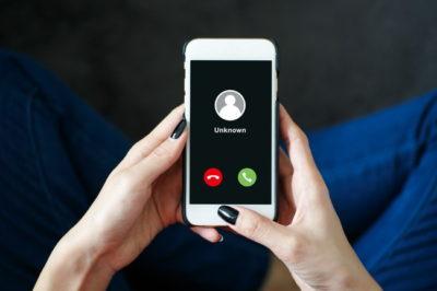 知らない番号からの着信のスマートフォンを持つ女性