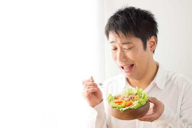 苦いレタスを食べる男性
