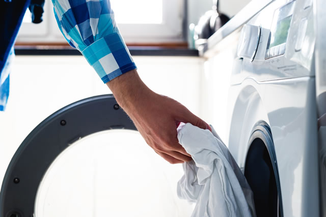 乾燥機に衣類を入れる男性